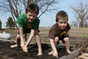 With the temps in the 70s the past few days, and the strong south wind, our pallet gardens were ready to be planted. So the boys helped me prepare them. They totally enjoyed getting their feet dirty doing so