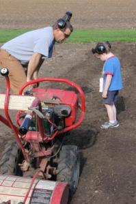 On May 15, we were very excited to be tilling in the garden. Steve and Sam discuss the process and are more then likely looking for a few worms. As Sam thinks this is an awesome thing to do.