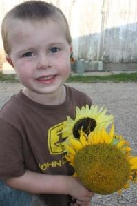 Sam with the sunflowers he picked.