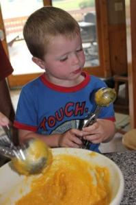 Sam couldn't wait to eat the squash. In fact he ate two bowls as soon as he was finished mixing it up. We used ice cream scoops to fill the muffin tins as we prepared them for freezing.